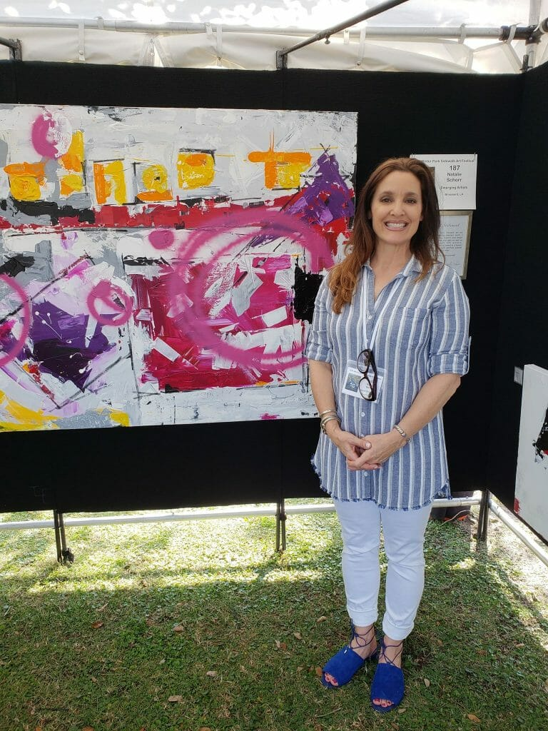 Emerging Artist Natalie Schorr poses alongside on of her works during the first day of the 60th Annual Winter Park Sidewalk Art Festival.